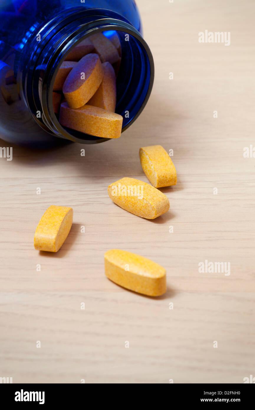 Botella azul amarillo de píldoras de vitaminas con algunos derramándose sobre la mesa Imagen De Stock