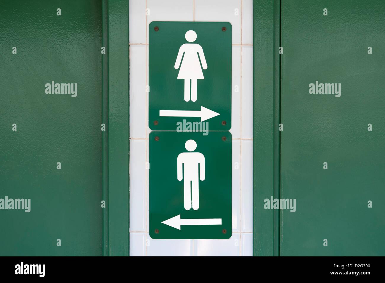 Señal verde con símbolos masculinos y femeninos dirigida a ir en direcciones opuestas Imagen De Stock