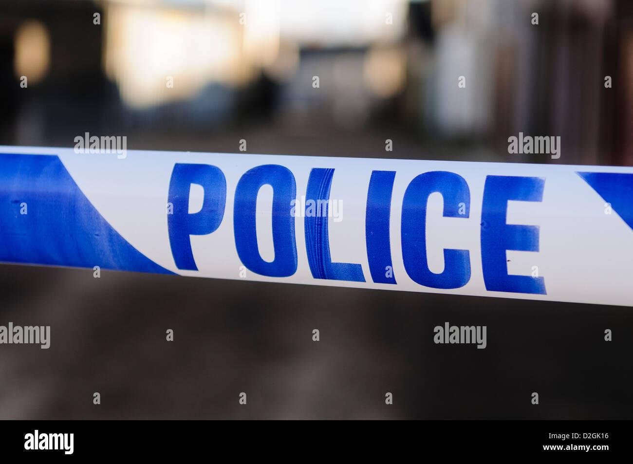 Cinta de la policía en el cordón a través de una escena de crimen Imagen De Stock