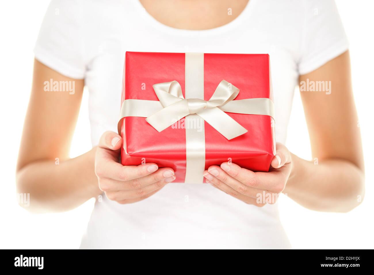 Primer plano de manos femeninas, mostrando y dando regalos con rojo papel de embalaje y la cinta blanca aislado Imagen De Stock
