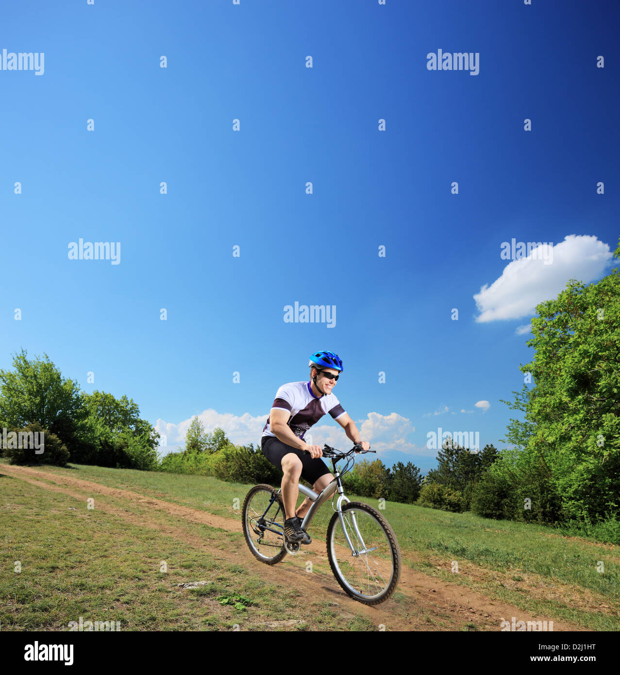 Ciclista macho montando una bicicleta de montaña cuesta abajo, tomada con una lente de basculación y de giro Foto de stock