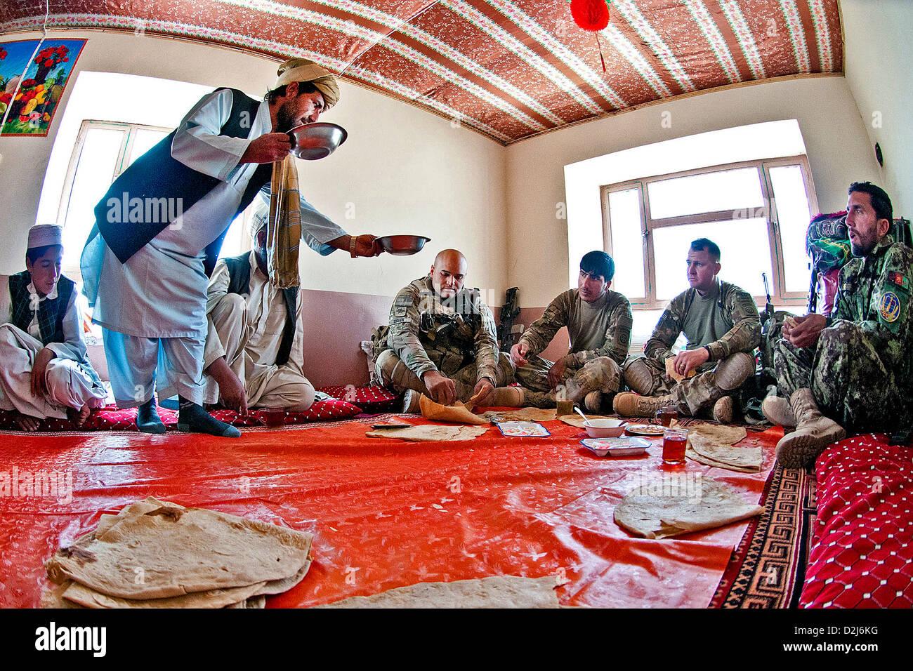 Un aldeano afgano ofrece alimento a los soldados del Ejército estadounidense durante una reunión con los Imagen De Stock