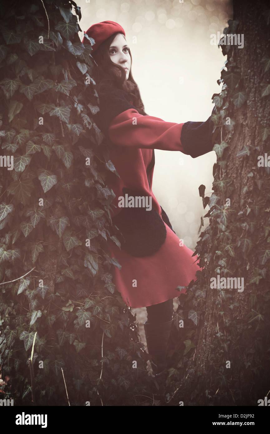 Una mujer con una chaqueta roja y sombrero entre dos troncos Imagen De Stock