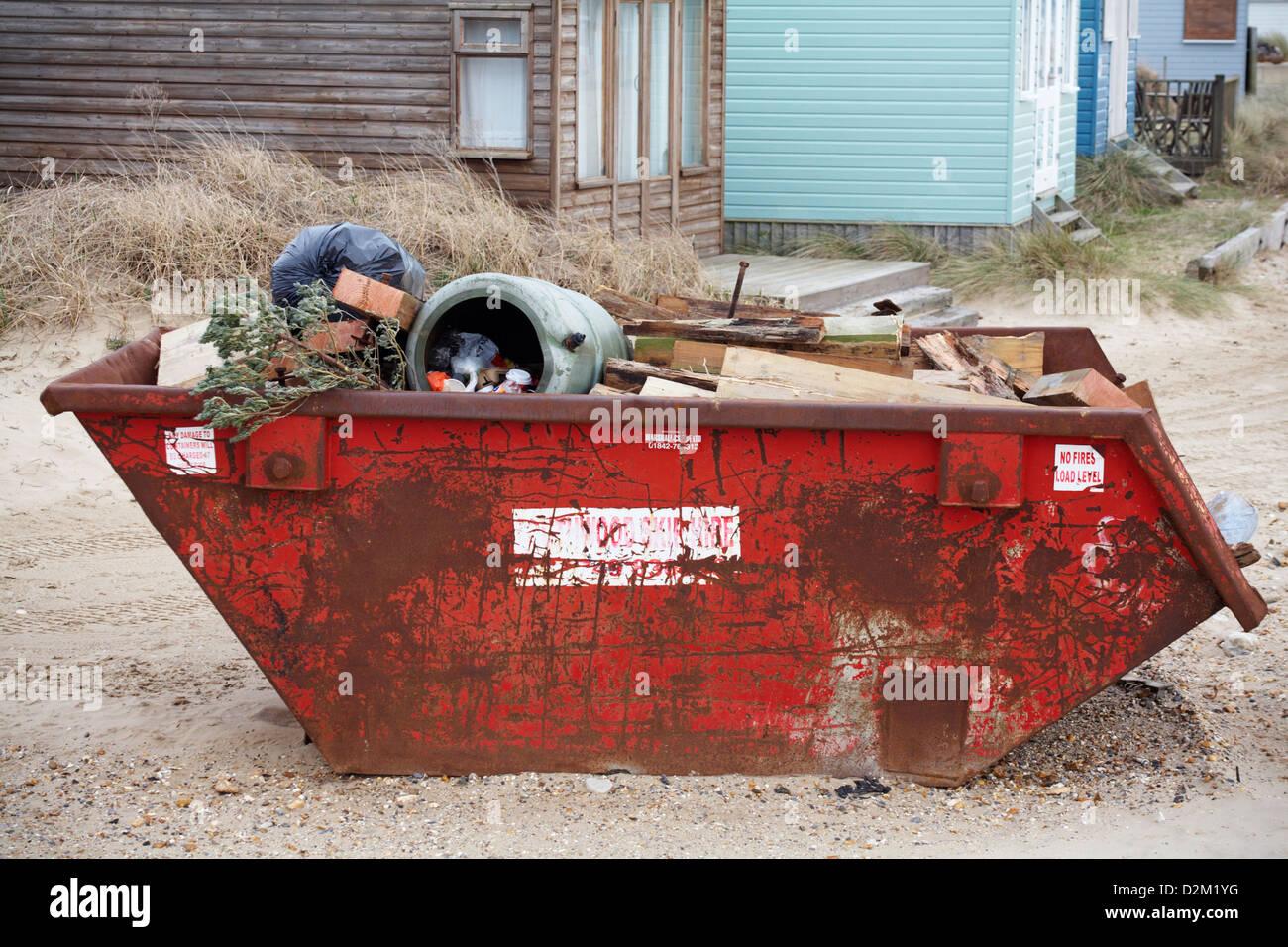 Skip para propietarios de cabaña en la playa basura en Hengistbury Head, Dorset en enero Imagen De Stock