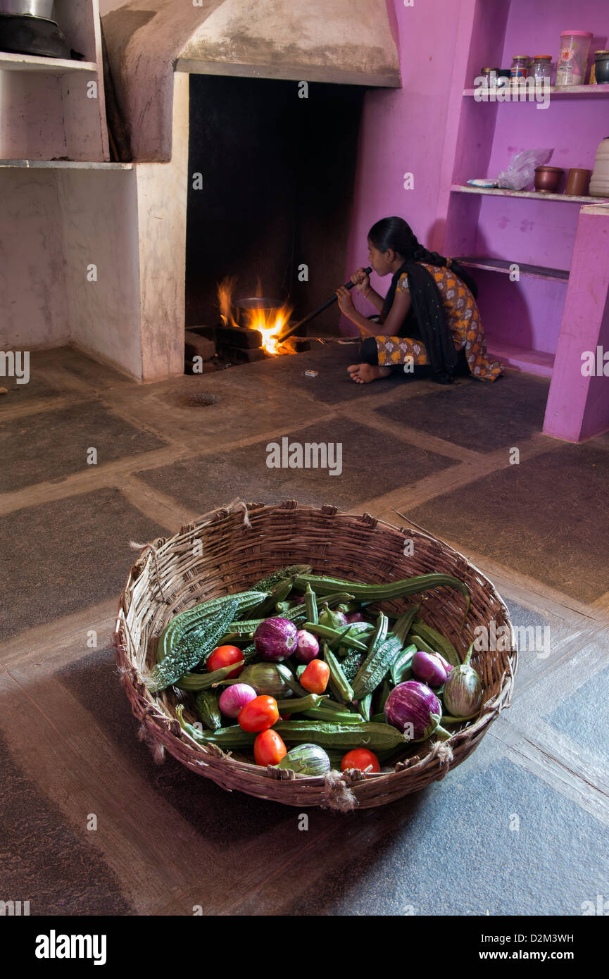 Cesta de verduras indio y una niña preparando el fuego en la cocina ...