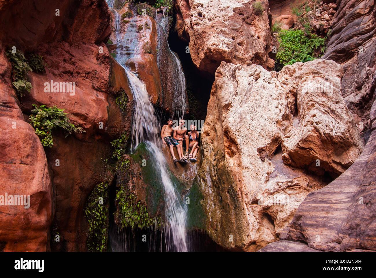 Los turistas bañarse en una cascada, visto mientras el rafting por el Río Colorado, el Gran Cañón, Imagen De Stock