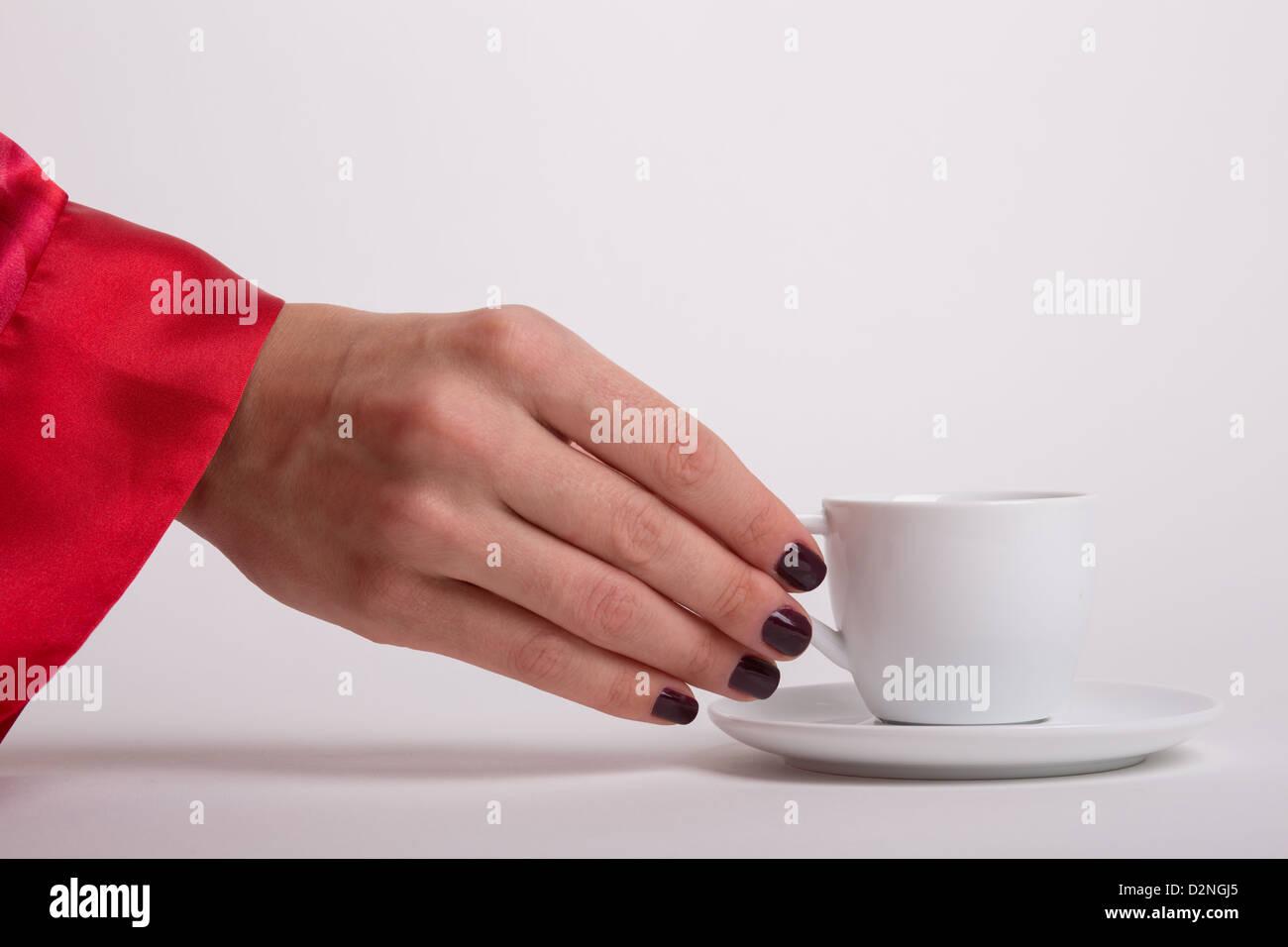Una mujer vistiendo una túnica roja llega para una taza de café espresso por la mañana blanco Foto de stock