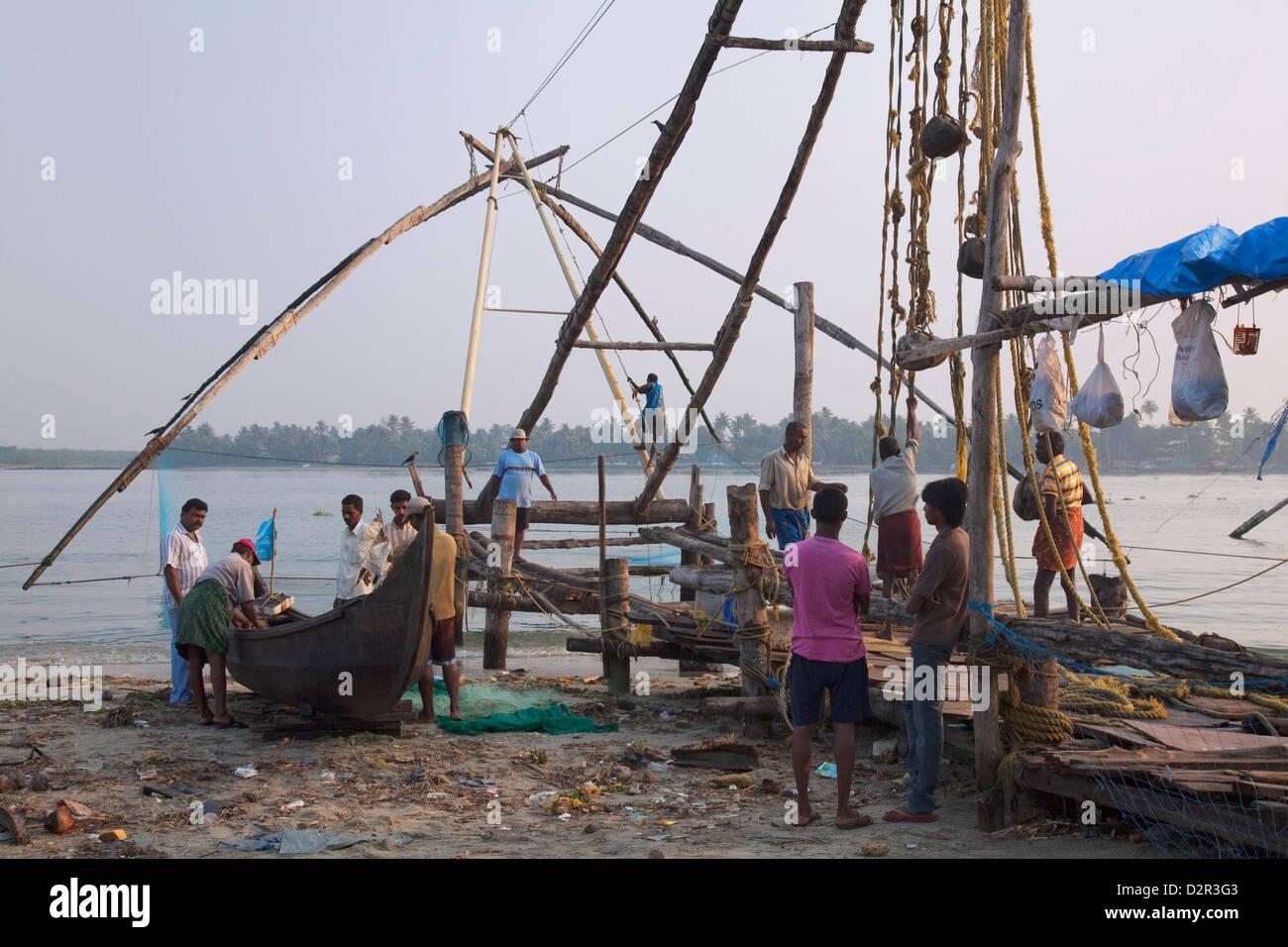 Los pescadores preparando embarcación tradicional chino y la red de pesca en la costanera en Kochi (Cochin), Imagen De Stock
