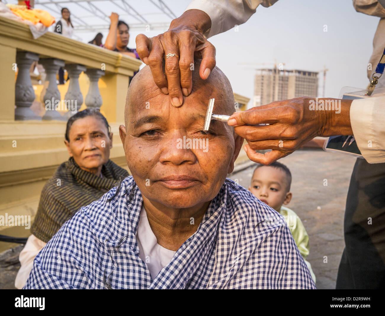 Phnom Penh, Camboya. El 31 de enero de 2013. Una mujer camboyana tiene sus cejas afeitados después del afeitado Foto de stock
