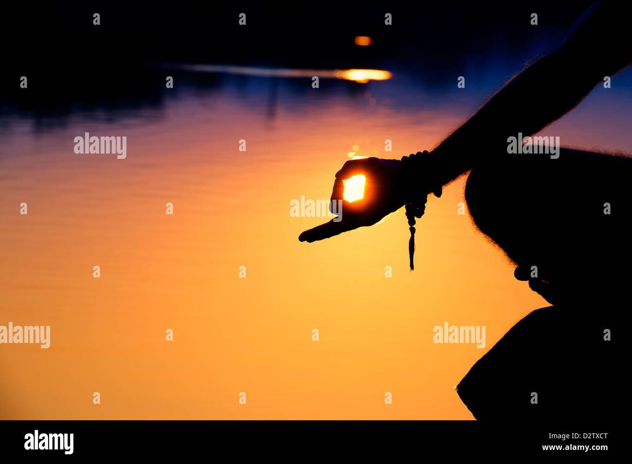 Silueta de un amanecer mans mano mientras meditando sobre rocas en una Indian Lake. En Andhra Pradesh, India Imagen De Stock