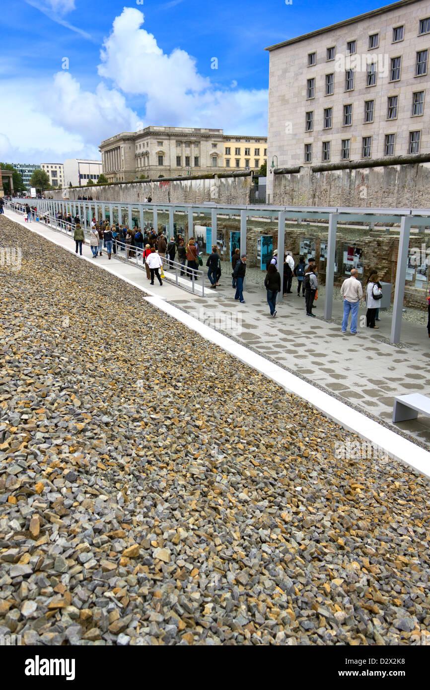 Los turistas que acuden a ver los restos del muro de Berlín con la exposición fotográfica. Imagen De Stock