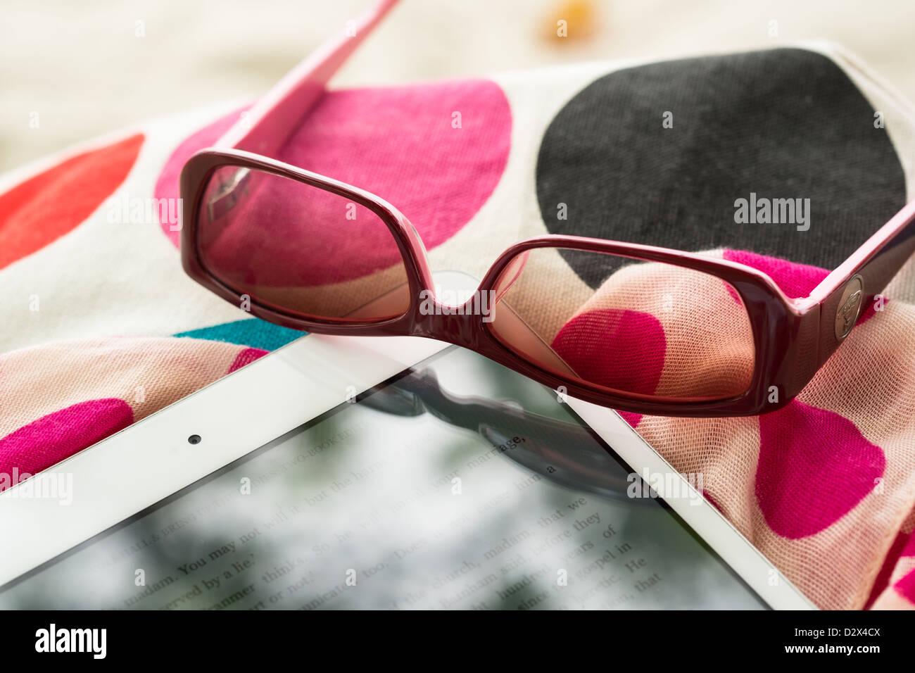 Cierre de un Mini Ipad blanco y gafas de sol en vacaciones Imagen De Stock