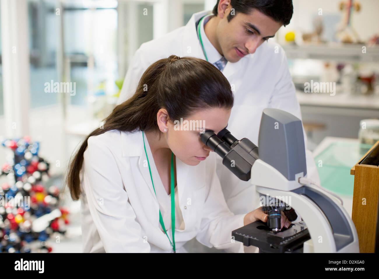 Científicos utilizando microscopio en laboratorio Imagen De Stock