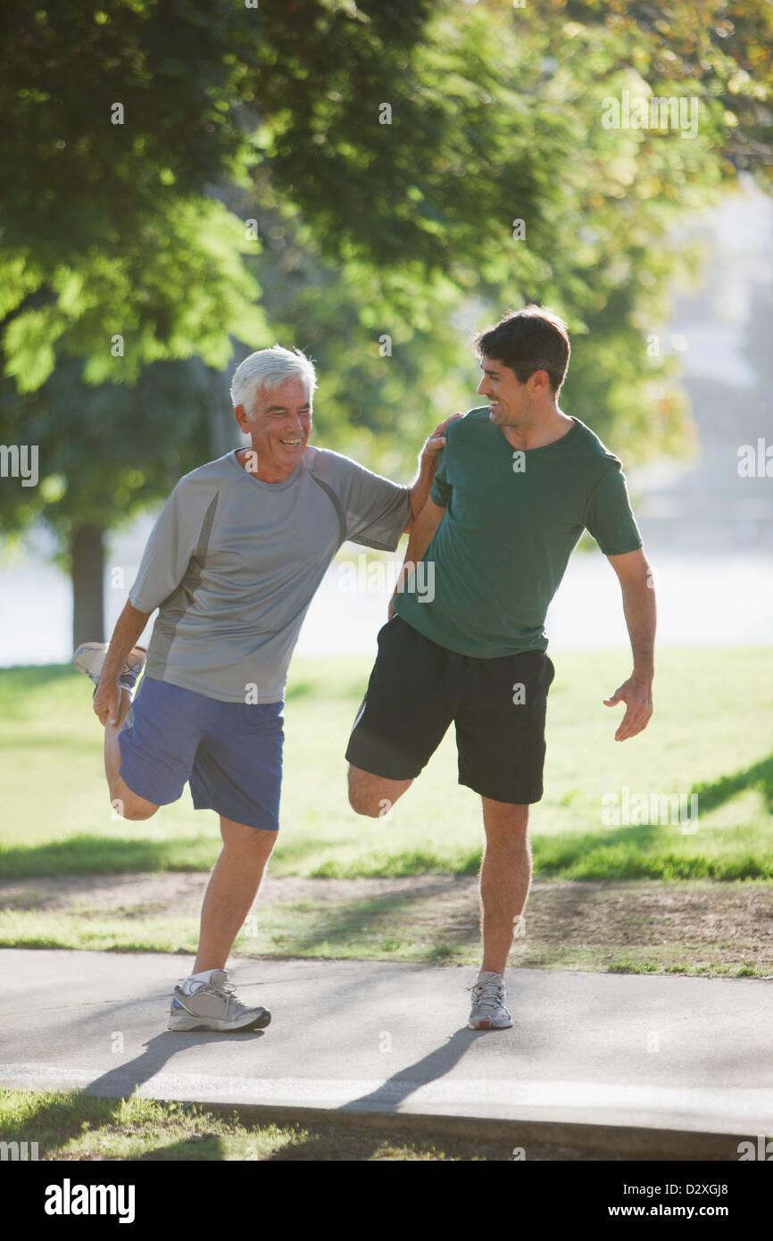 Hombre mayor estiramiento con entrenador Imagen De Stock