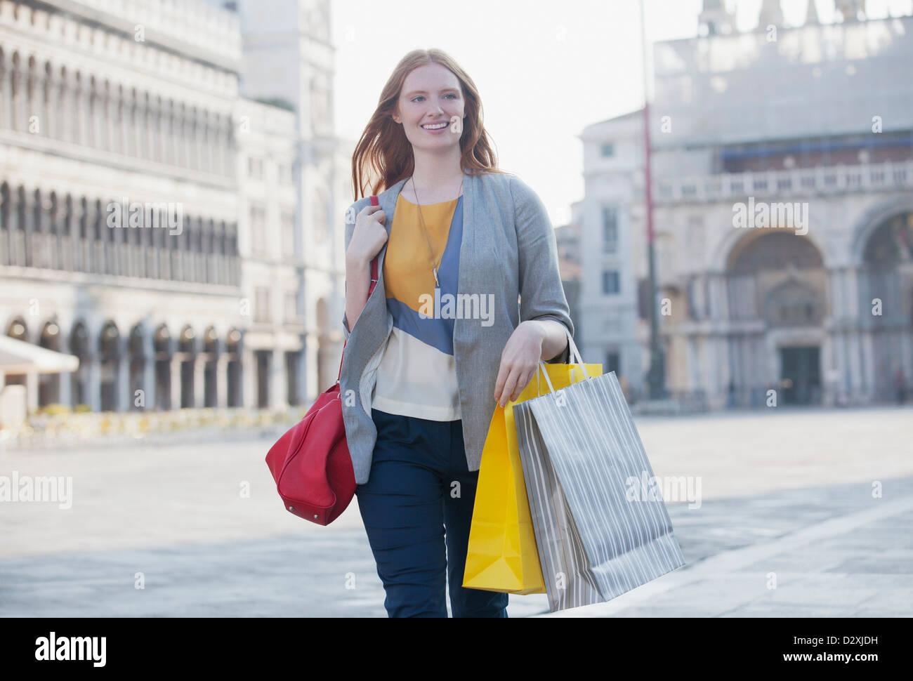Mujer sonriente llevando bolsas de la compra a través de la plaza de San Marcos en Venecia. Imagen De Stock