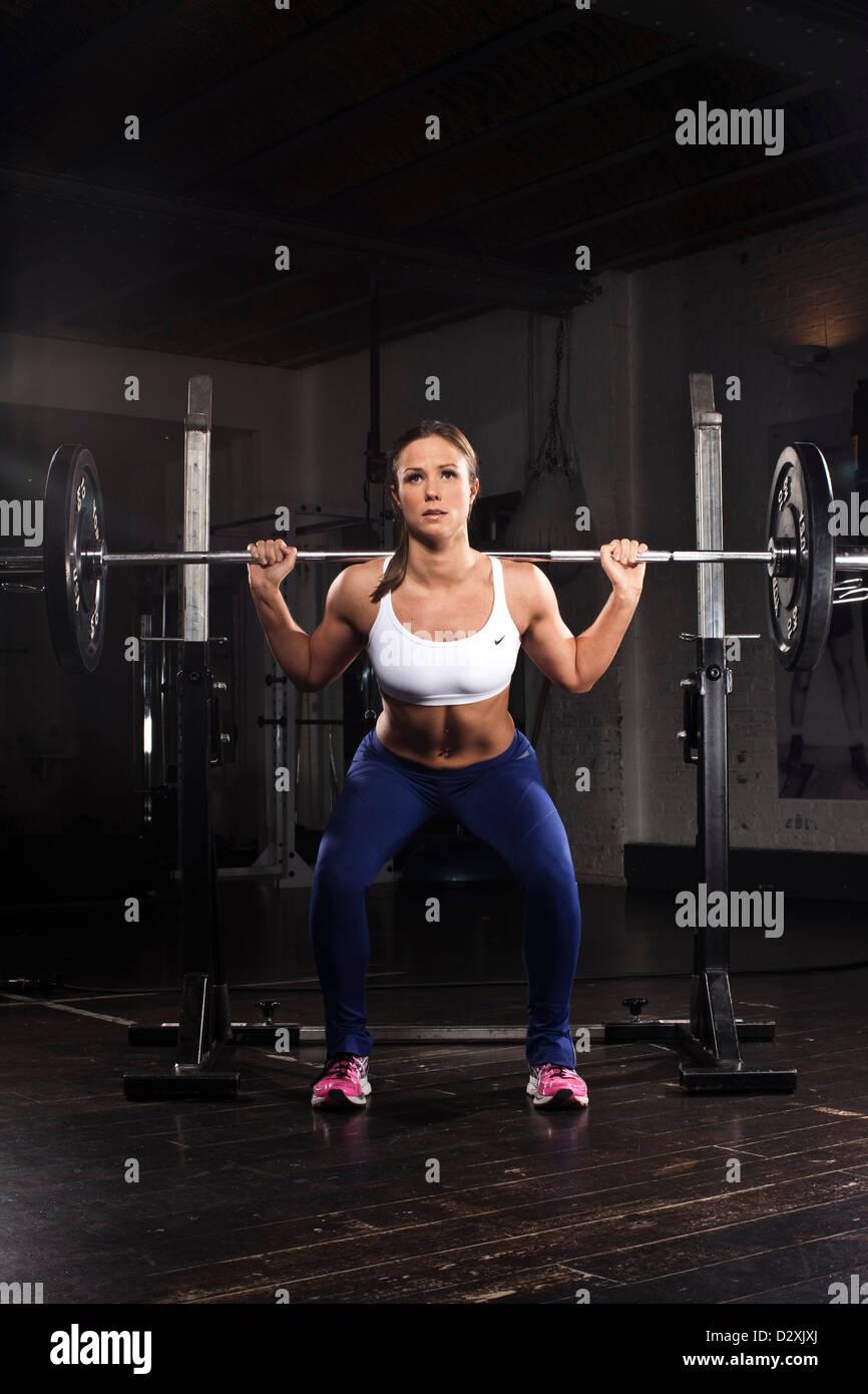 La construcción del cuerpo femenino, el levantamiento de pesas en el gimnasio. Imagen De Stock