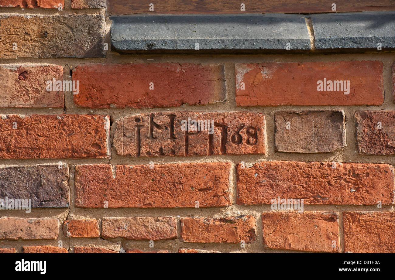 Iniciales y la fecha grabada en los ladrillos en un granero recientemente renovado en la Inglaterra rural. Imagen De Stock