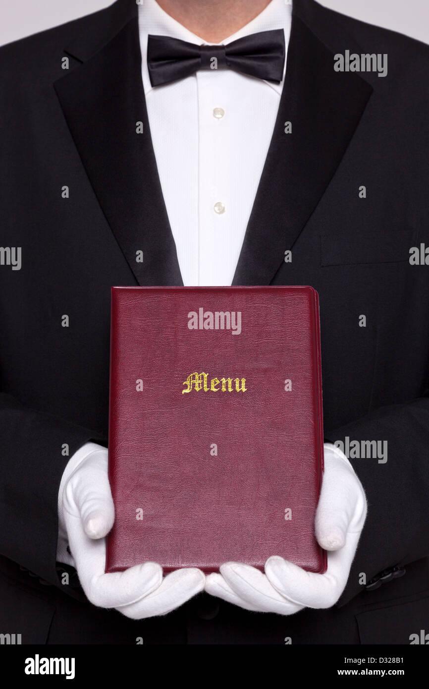 Camarero sosteniendo una carpeta de menú en un restaurante. Imagen De Stock