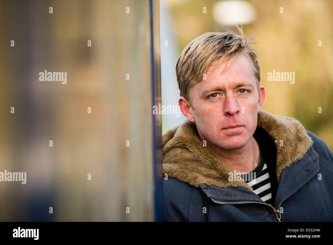 Un hombre rubio slim macho, finales de 30's y principios de 40's, solo solo solo, mirando triste UK Imagen De Stock