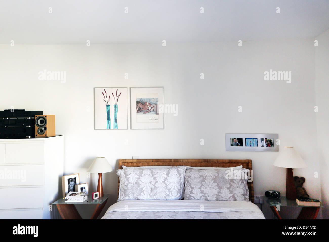 Dormitorio cama con mesitas de noche y la imagen en la pared Cheltenham Gloucestershire Inglaterra Imagen De Stock