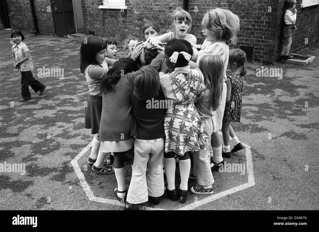 Los niños de la escuela las niñas jugando juegos para los niños pequeños. 1970 El sur de Londres. Imagen De Stock