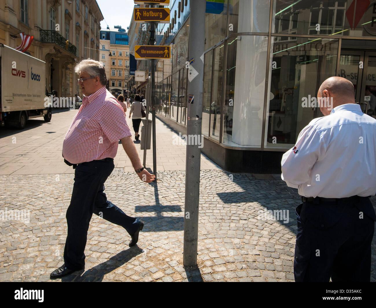 Un hombre en edad midlle caminando calle soleada Foto de stock