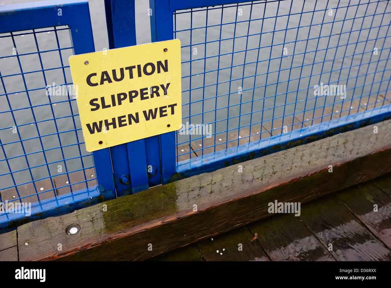 Precaución slippery when wet signo en paseo de madera pasarela North Vancouver, BC Canadá Imagen De Stock
