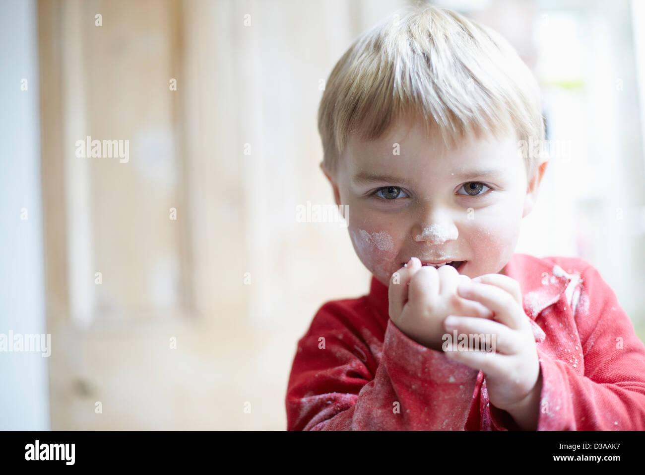 Los niños con el rostro cubierto en la harina en la cocina Imagen De Stock