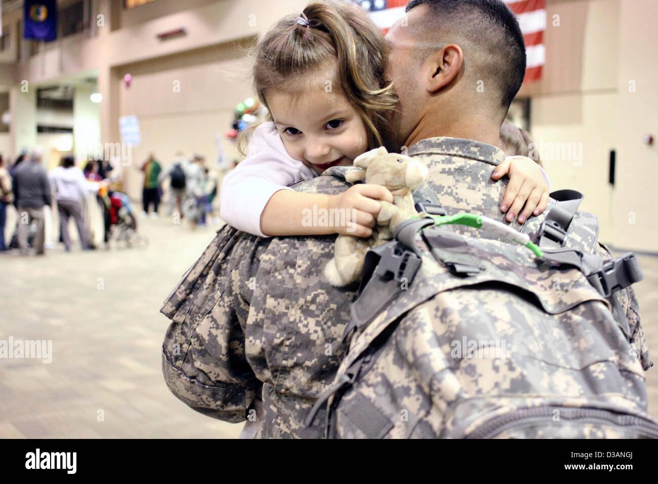 US Army Spc. José Cisneros abraza a su hija Rosalyn tras regresar de un despliegue de nueve meses a Kuwait el 14 de febrero de 2013 en Fort Benning, GA. Más de 300 soldados fueron reunidos con sus familiares y amigos justo a tiempo para celebrar el Día de San Valentín. Foto de stock