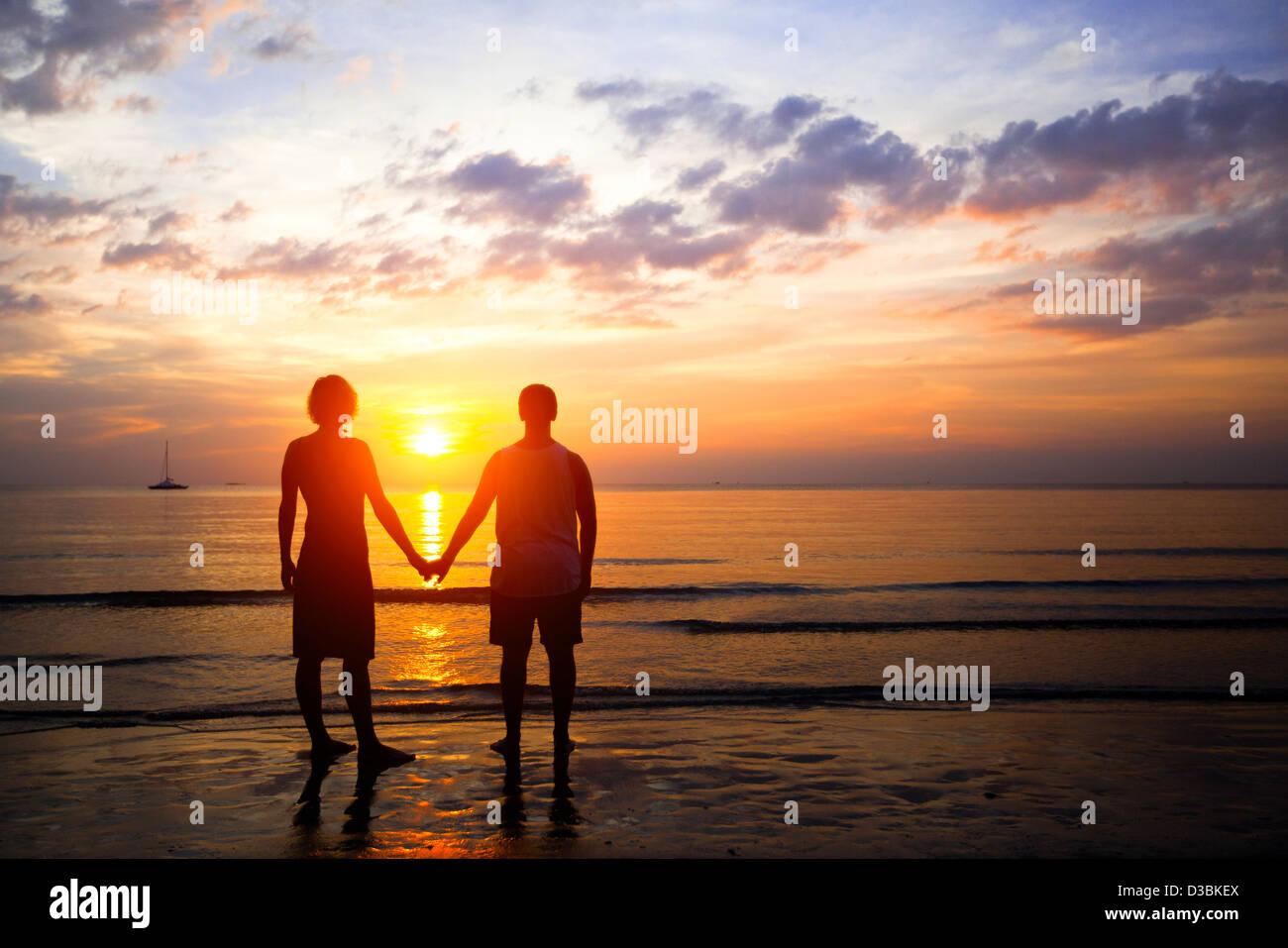 Pareja joven en amor al atardecer a la orilla del mar Foto de stock