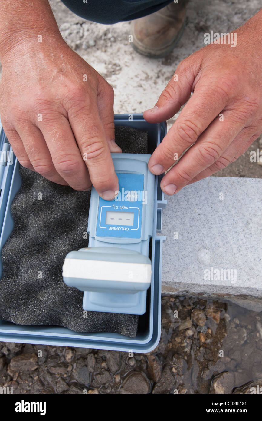 Ingeniero que trabaja con cloro monitor en muestra de agua Foto de stock