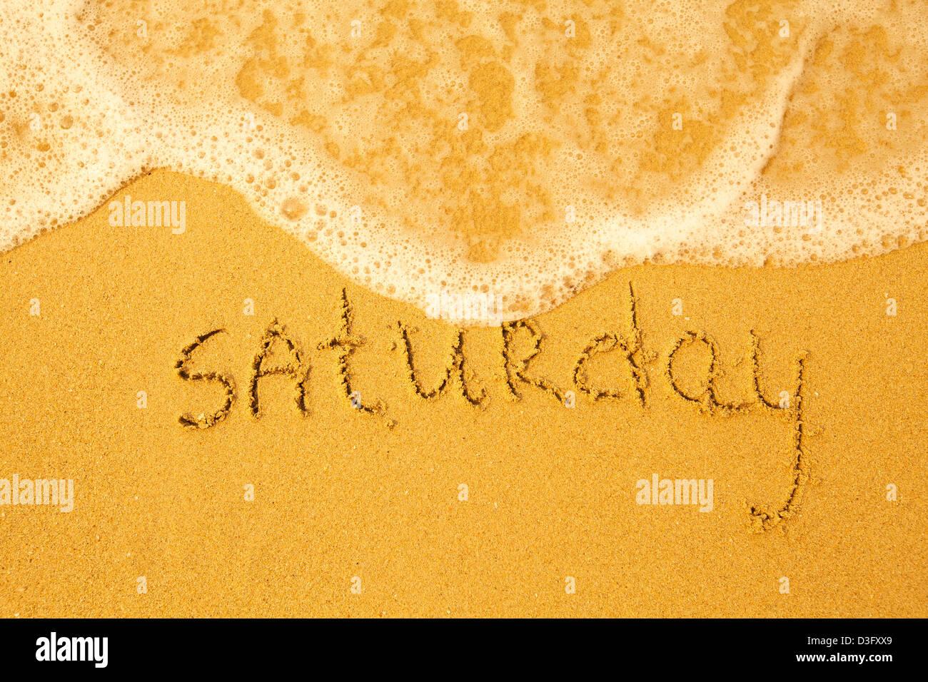 Sábado - escrito en la arena de la playa de suave textura - ola del mar Imagen De Stock