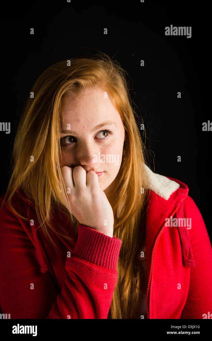 Un tímido y nervioso, 16 de 17 años de pelo rojo motea enfrenta adolescente, morder sus uñas UK Imagen De Stock