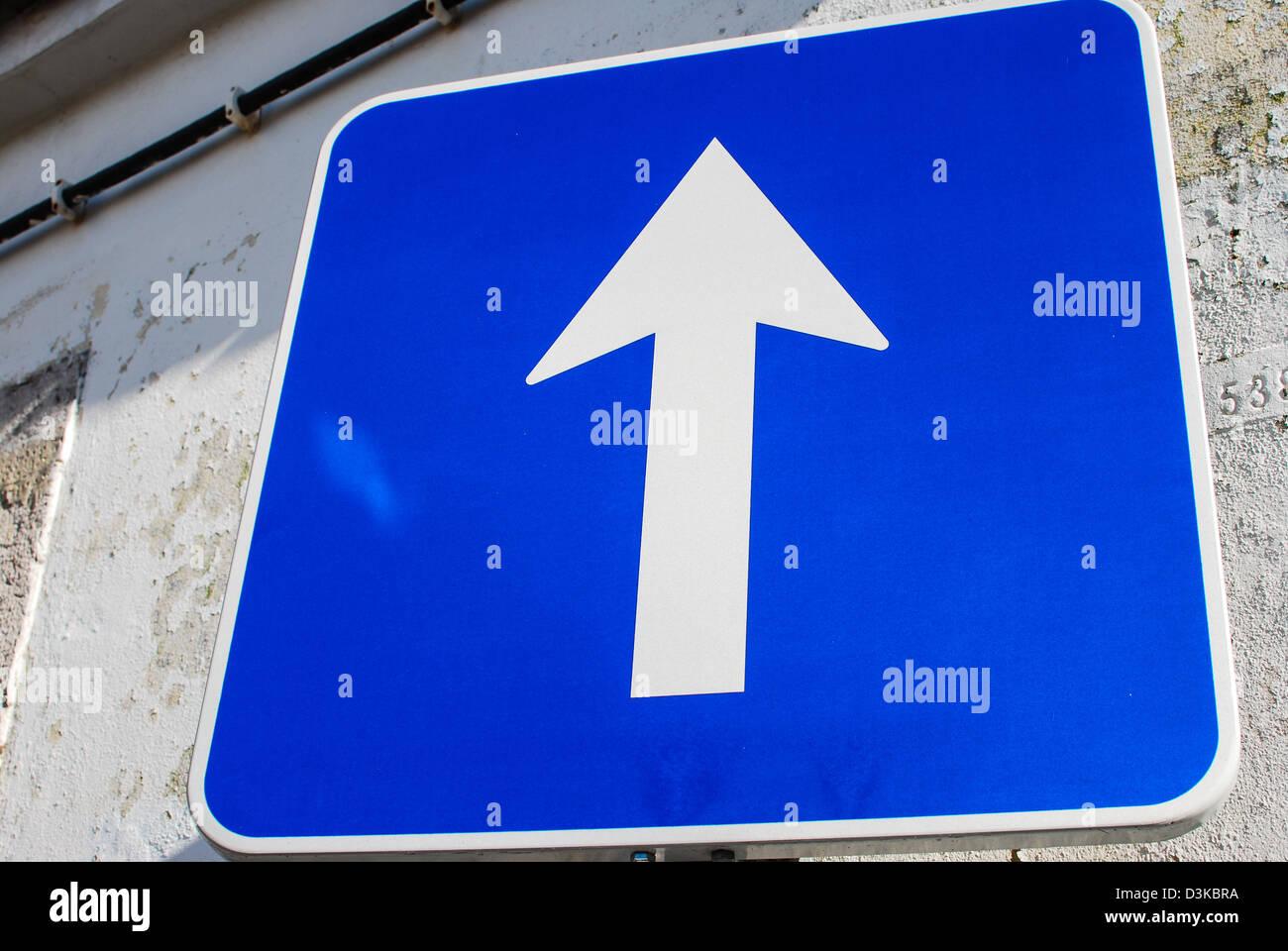 Señal azul con la flecha de dirección blanco grande Imagen De Stock