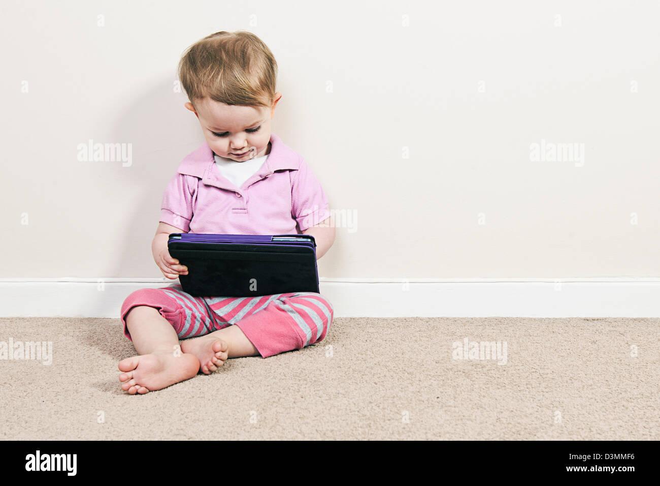 Baby Girl en el iPad Mini Imagen De Stock