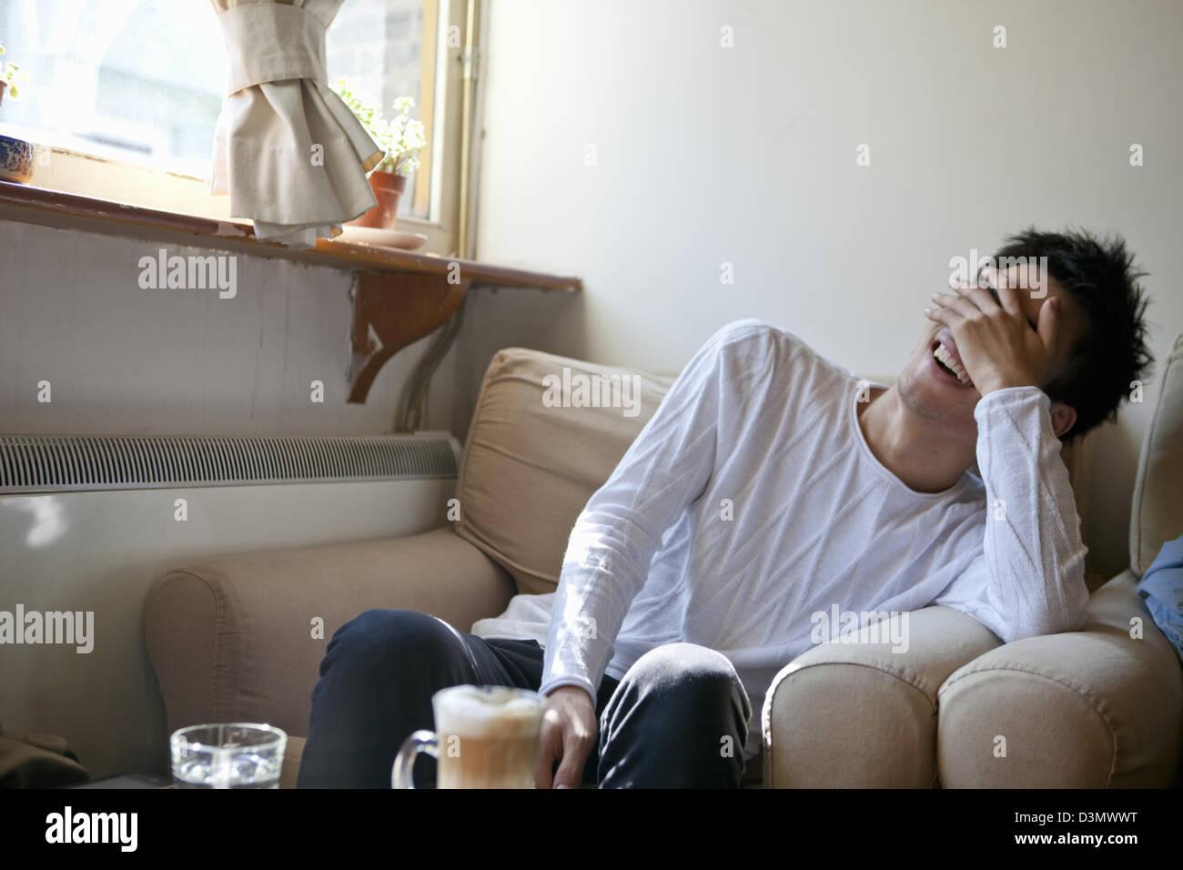 Embarrassed joven hombre chino cubra la cara riendo Imagen De Stock