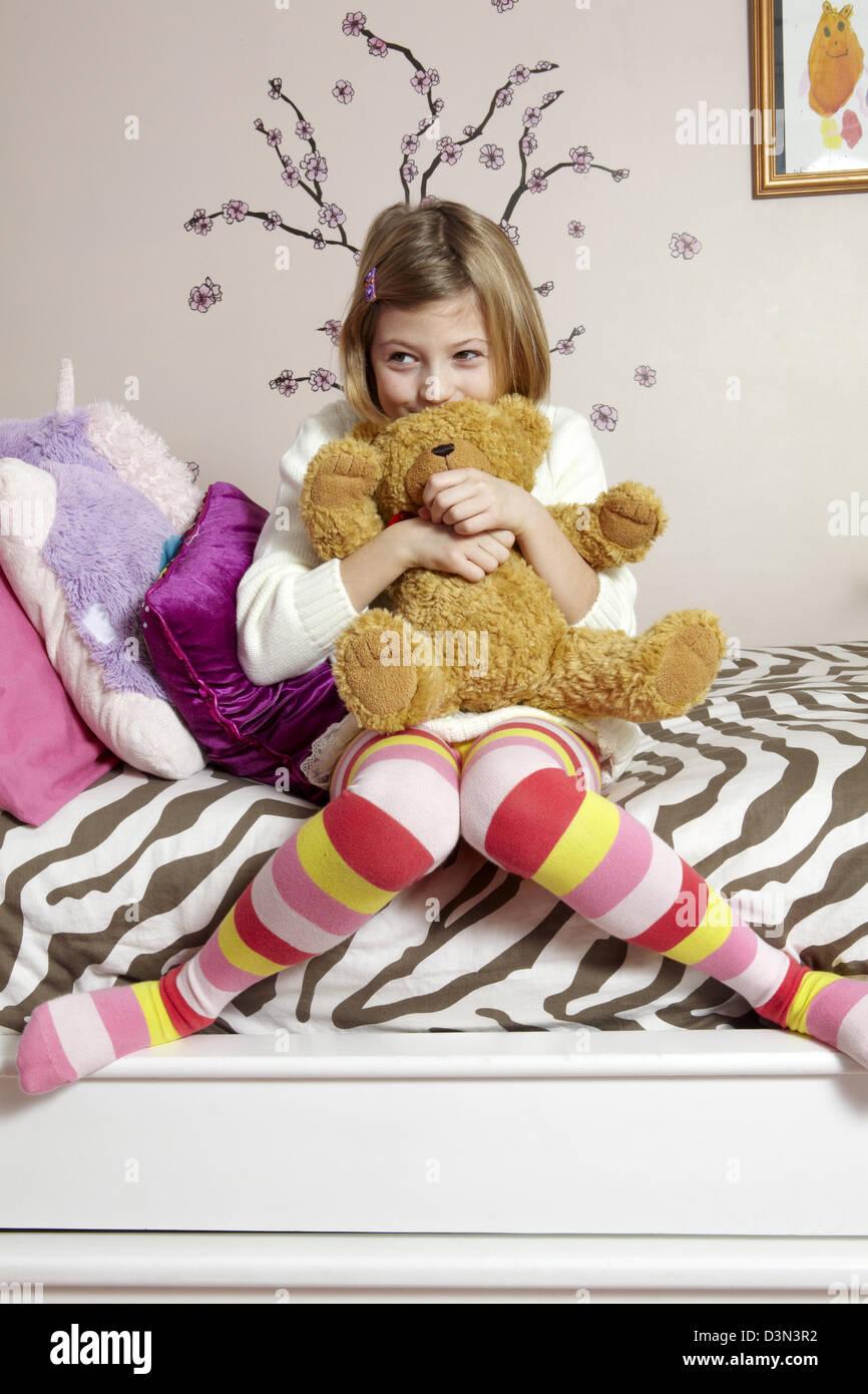 Niña de 9 años sentada en su cama, abrazando a un oso de peluche Imagen De Stock