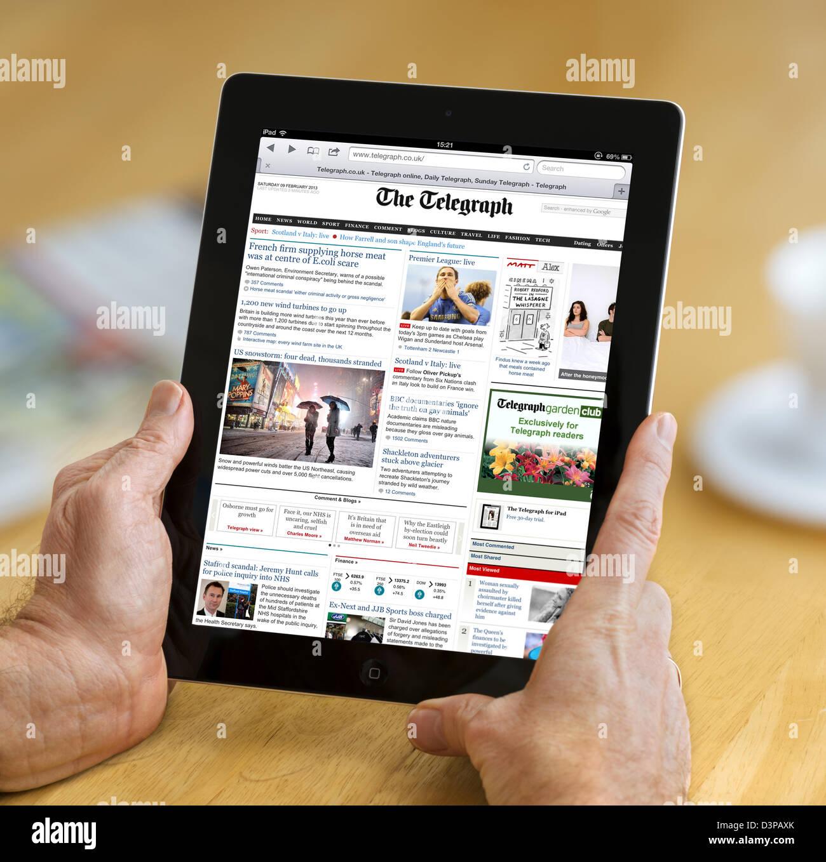 La lectura de la edición Internet del telégrafo diario online en un iPad de 4ª generación, REINO Imagen De Stock