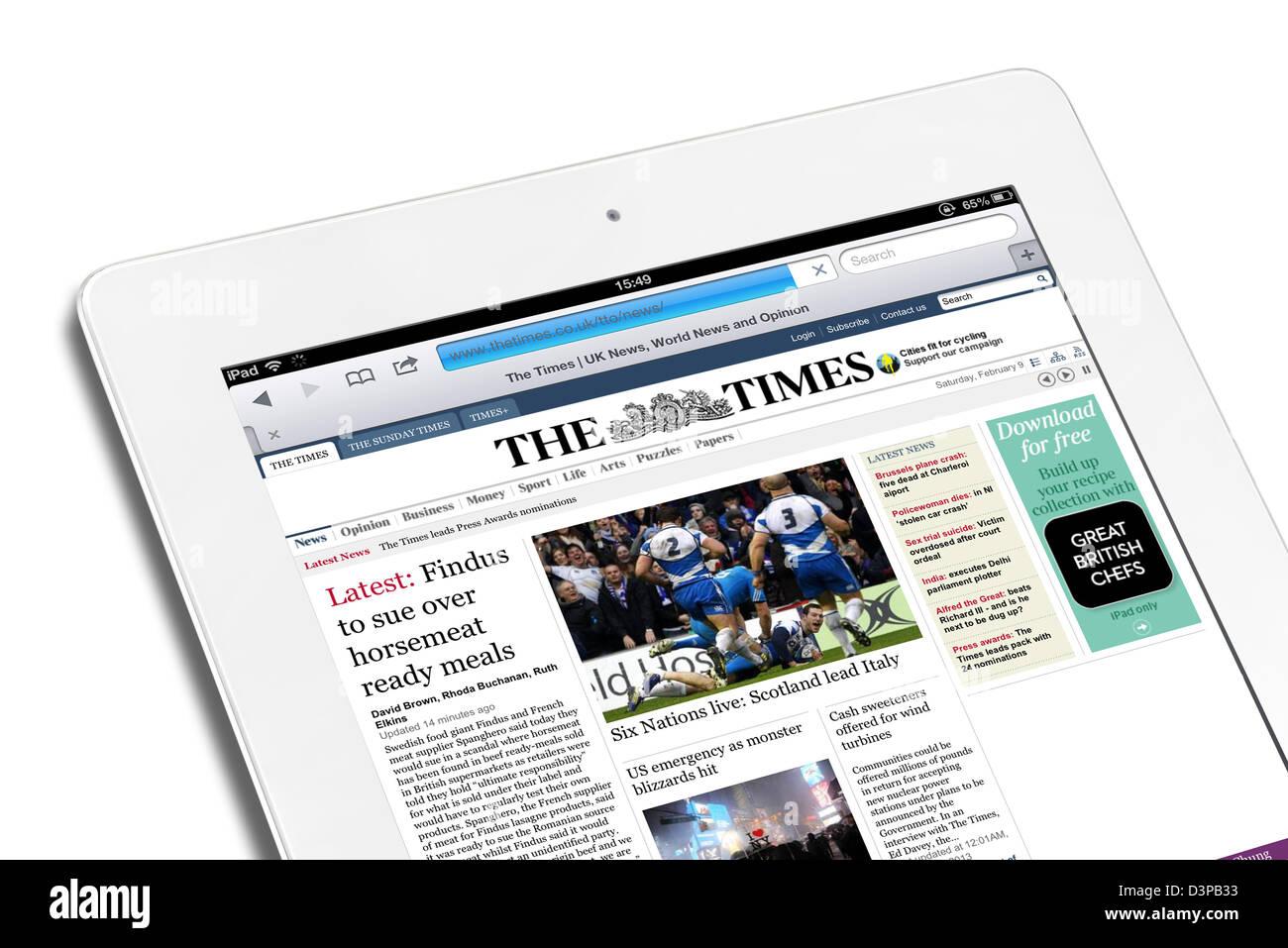 La lectura de la edición de internet de el periódico The Times sobre un blanco de cuarta generación, Imagen De Stock