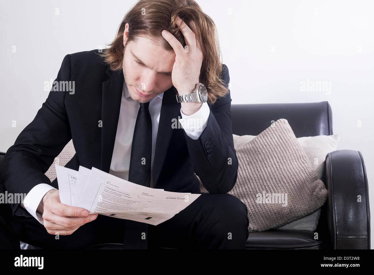 Hombre blanco en un elegante traje de negocios con una mano en su largo pelo  marrón 761c9b0c935