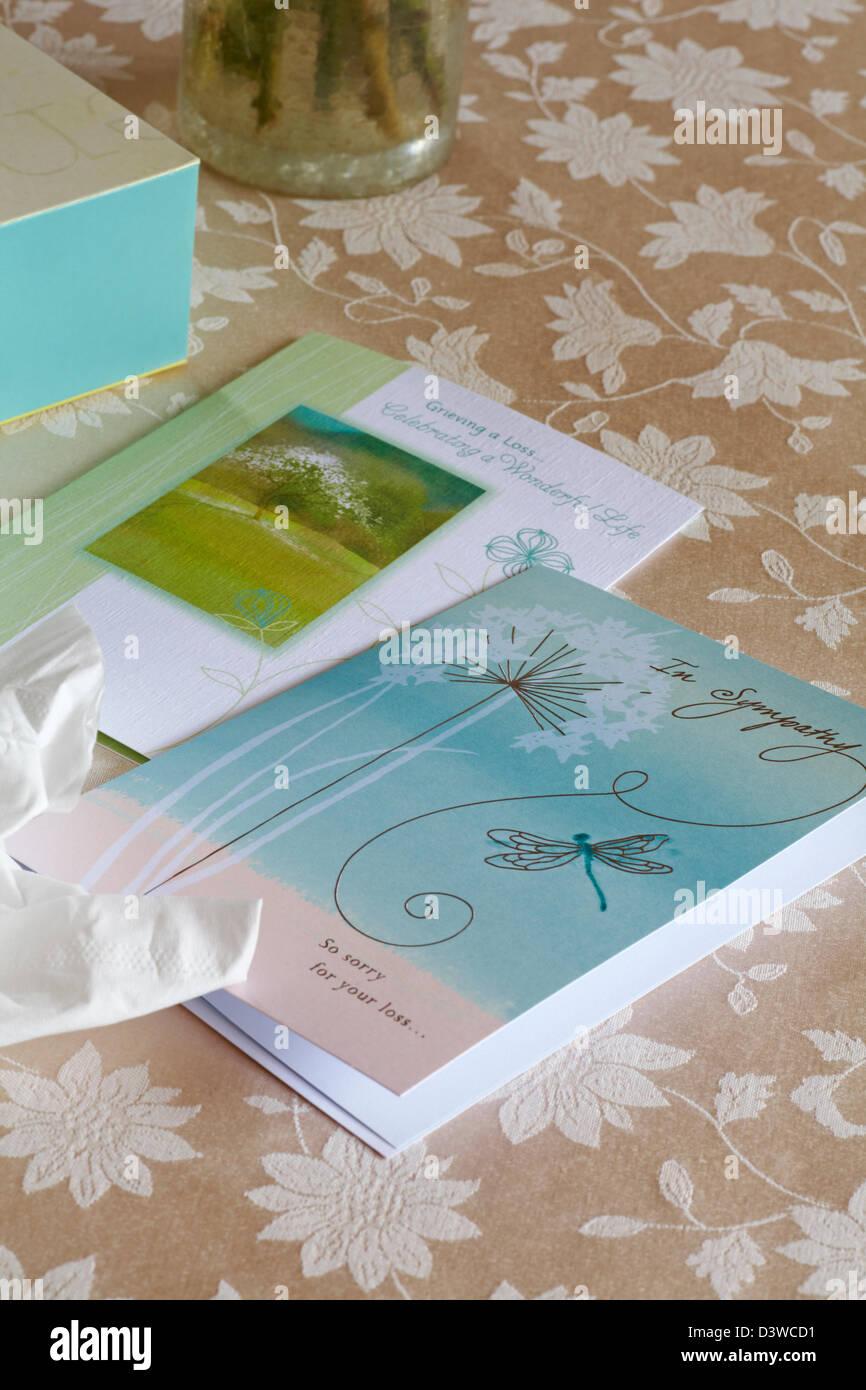Tarjetas de pésame y de la caja de pañuelos en un mantel. Imagen De Stock