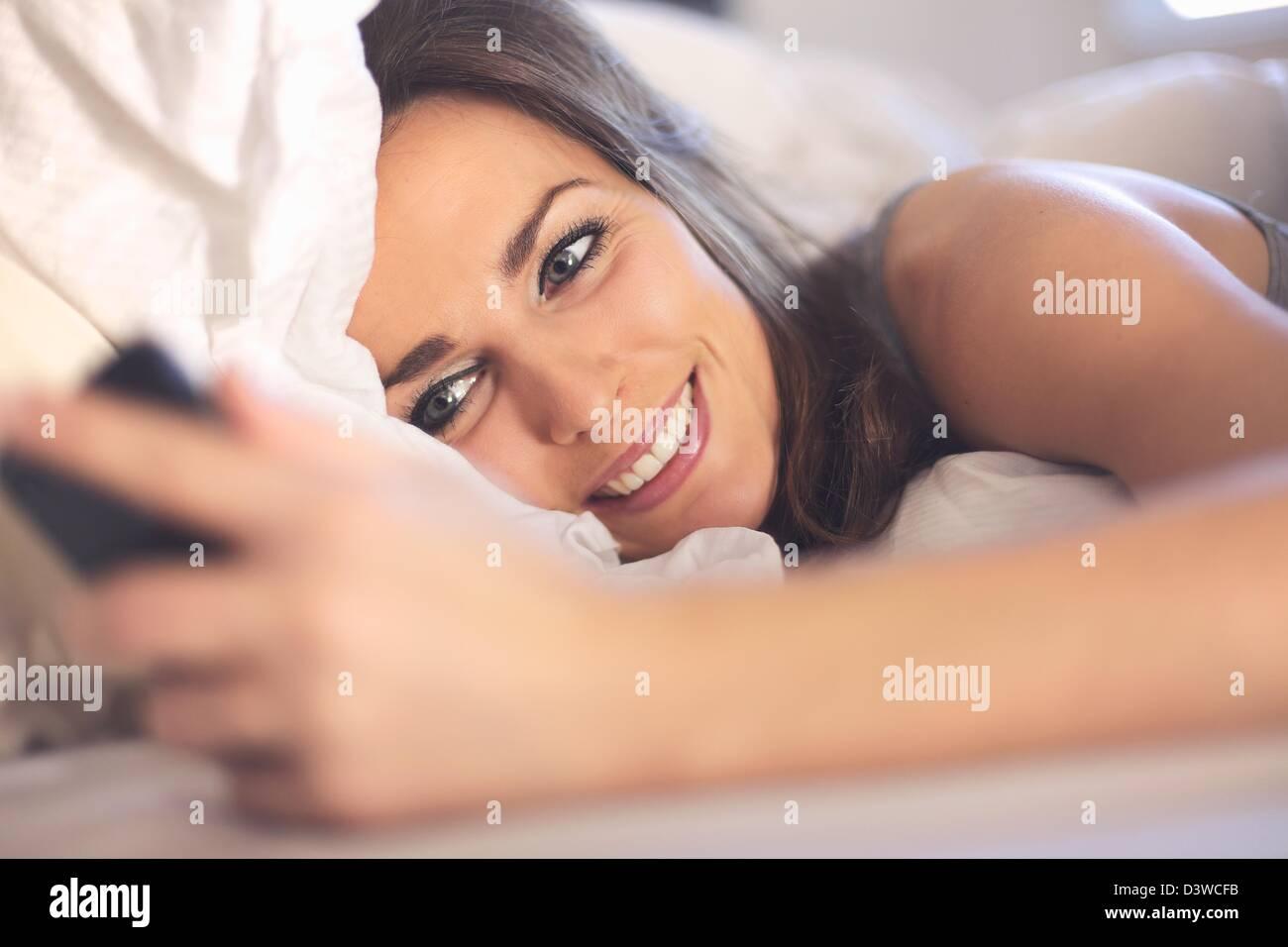 Feliz mujer acostada en la cama sonriendo mientras lee un mensaje de texto de alguien Imagen De Stock
