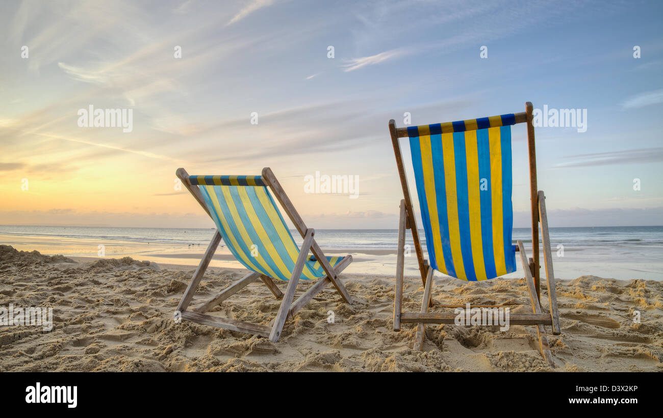 Dos tumbonas vacías en una playa al amanecer. Foto de stock