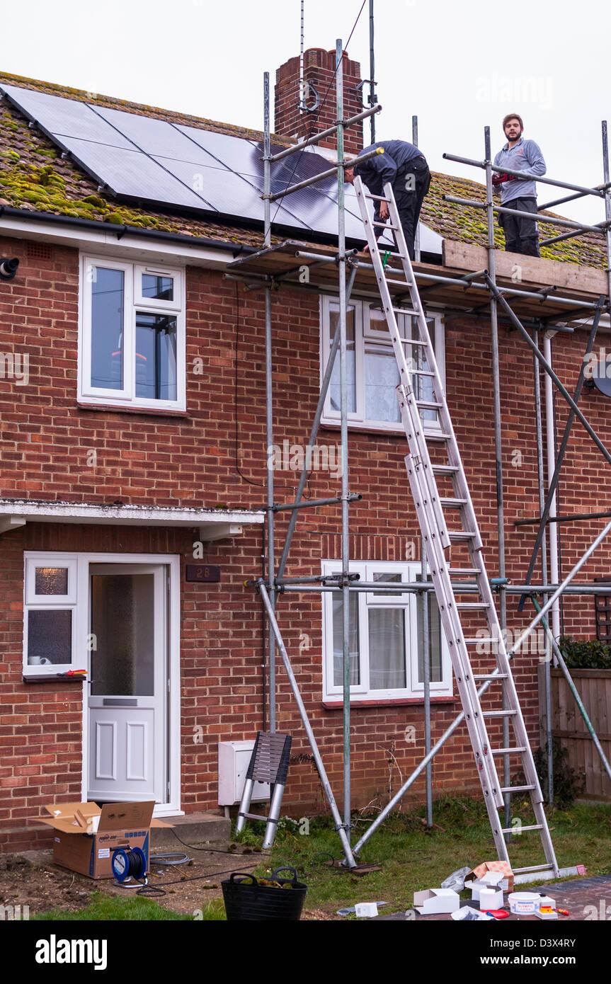 Dos hombres de colocar paneles solares en el tejado de una casa en el Reino Unido Imagen De Stock