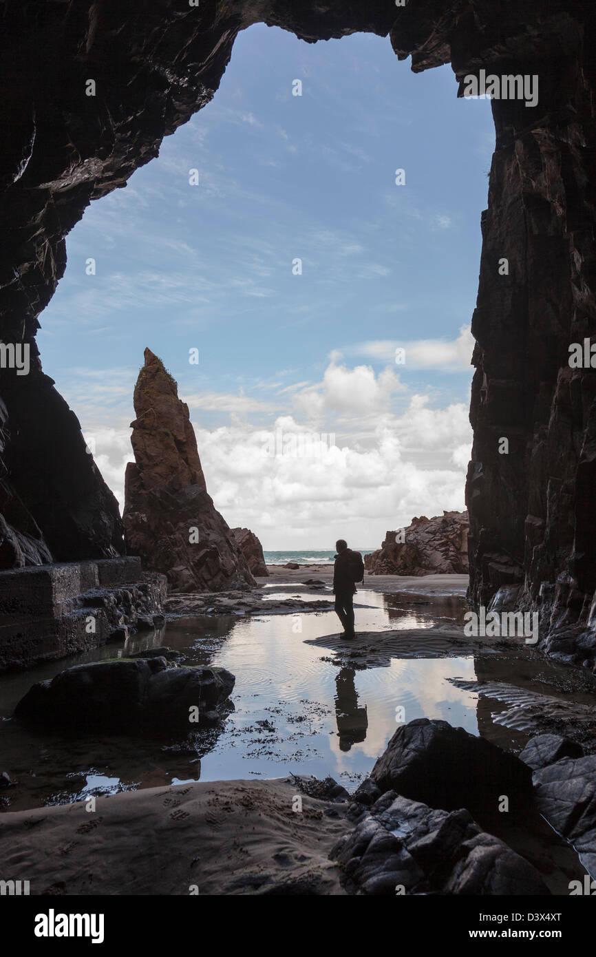 Roca de agujas con una persona de pie en la cueva Plemont, Jersey, Islas del Canal, REINO UNIDO Imagen De Stock