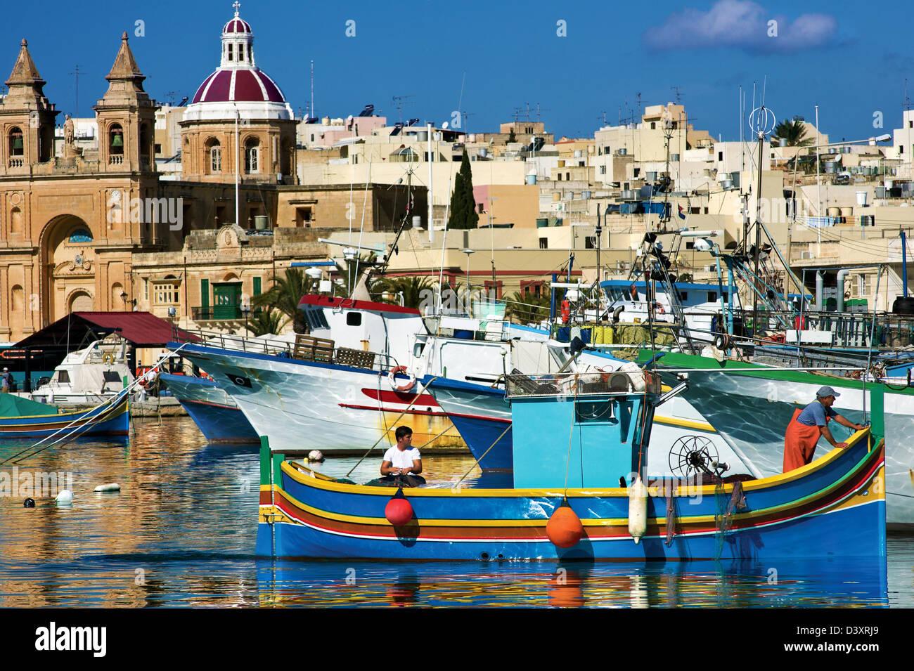 Los pescadores en el tradicional barco pesquero maltés.Marsaxlokk, Malta. Foto de stock