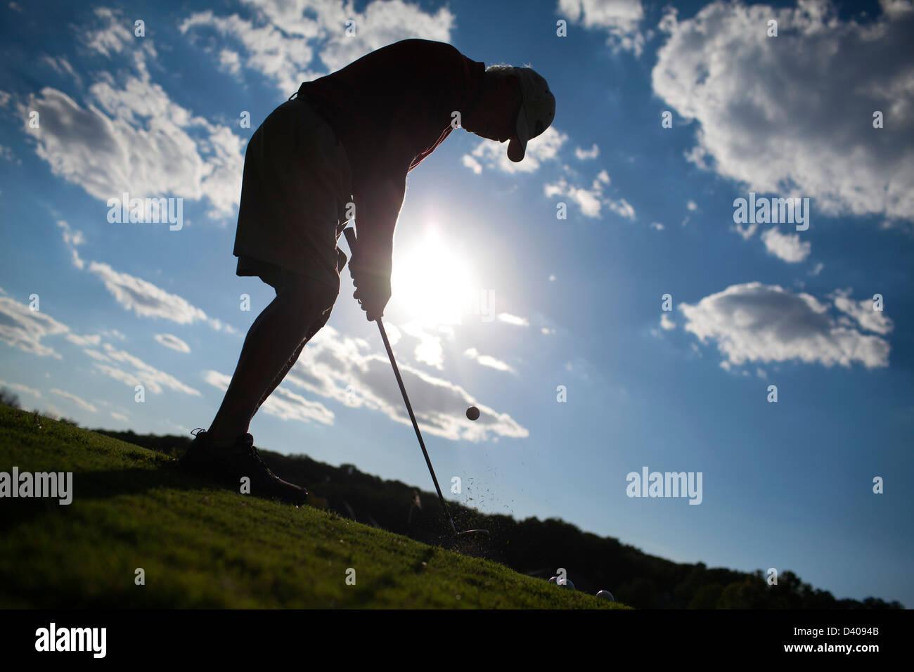 Un golfista senior parcelas en una zona verde en el campo de prácticas de golf. Imagen De Stock
