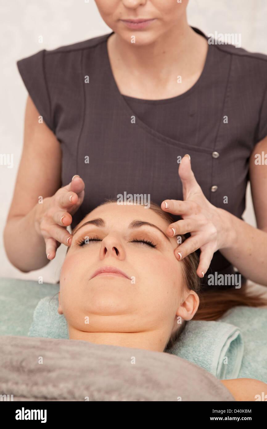 Una mujer joven con los puntos de presión en su templo el masaje. Imagen De Stock