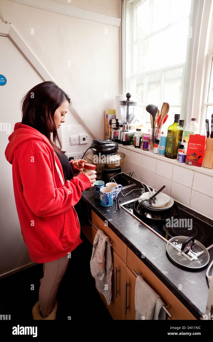 Mujer, estudiante de la universidad de hacer café en su cocina, Clare College, Universidad de Cambridge UK Foto de stock
