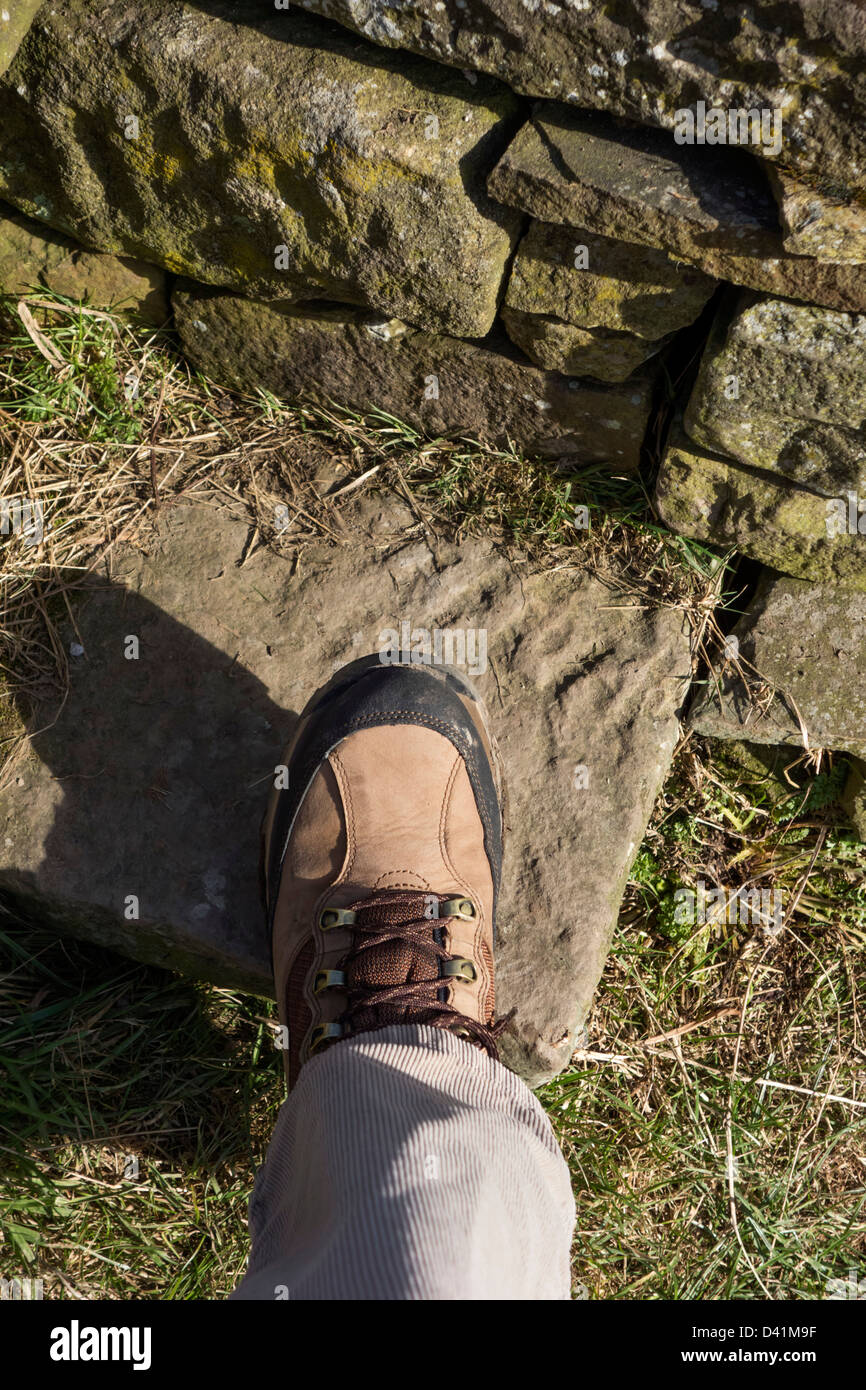 Cerca de caminar boot en el paso de una piedra stile en una acera pública, REINO UNIDO Imagen De Stock